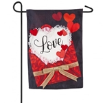 "Doily ""Love"" message on white sticking up from red envelope with tan ribbon appliqued on black, poly-burlap garden flag"