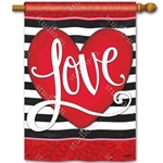 Big red heart with Love written on it against a background of black and white stripes