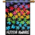 brightly colored puzzle pieces arranged against a black background with the words Autism Aware in white caps across bottom