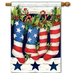 flag with stockings in red, white, blue stars and stripes,  hung by hearth filled with holly and candy canes