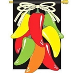 Red, orange, yellow, green chili peppers hanging from a white bow against a black background