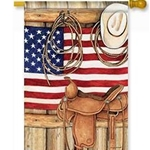 Cowboy hat, rope and saddle, in tan shades,  superimposed on US flag in background all against a wooden wall.